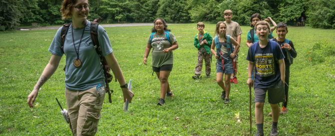 A teacher naturalist leads a group of summer campers