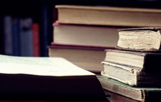 An open book next to two stacks of books