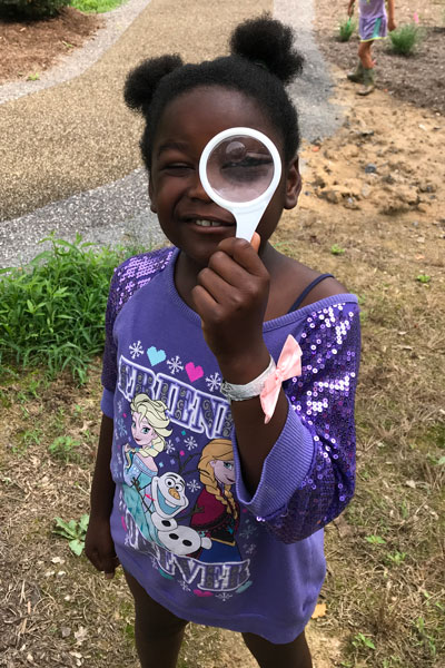 Little girl holds a magnifying glass to her eye while smiling at the camera