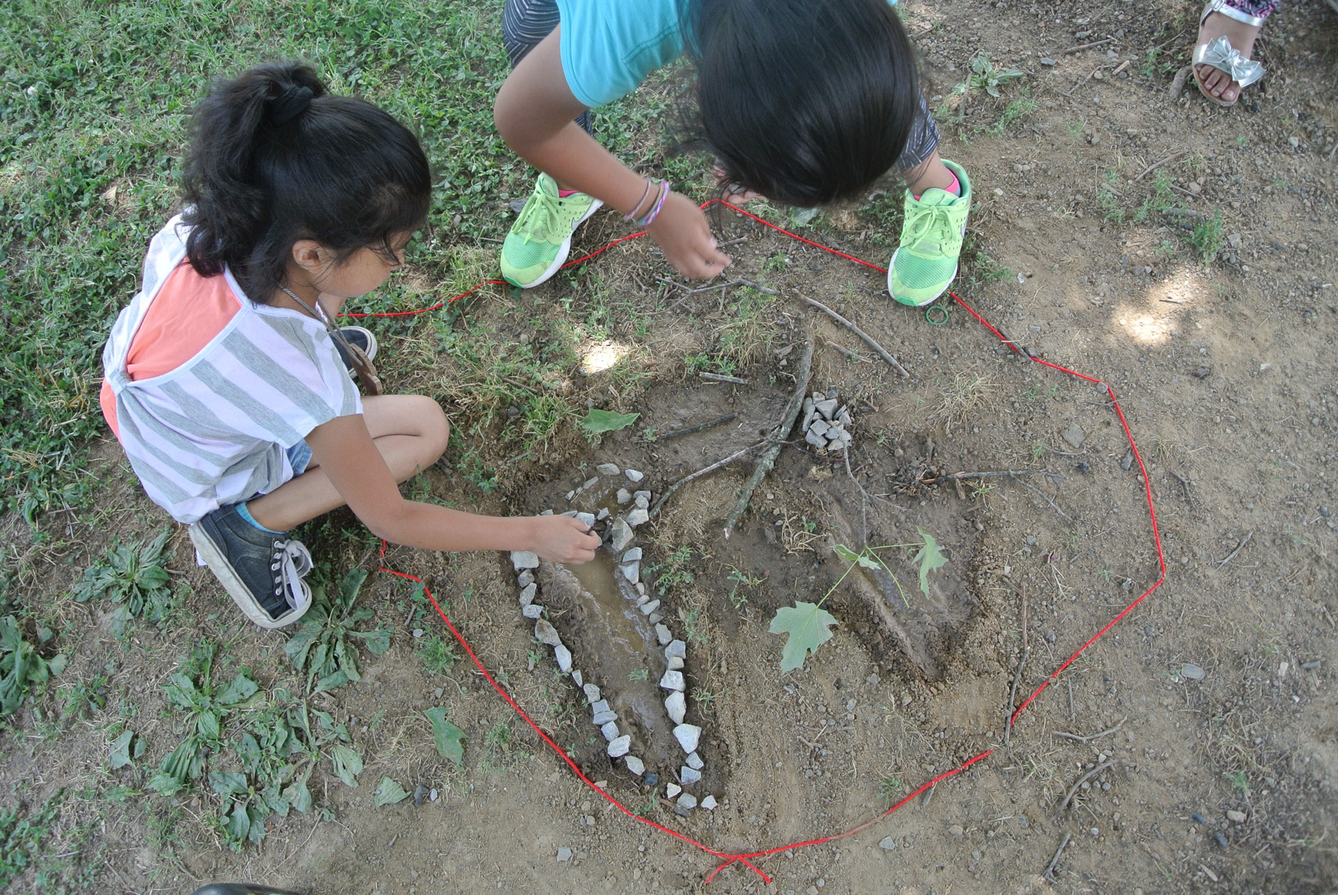 Students uses objects found in nature and a string to learn outside