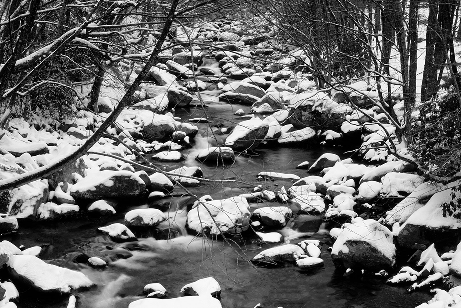 Black and white photo of snow and a mountain stream. Photo by Willard Clay