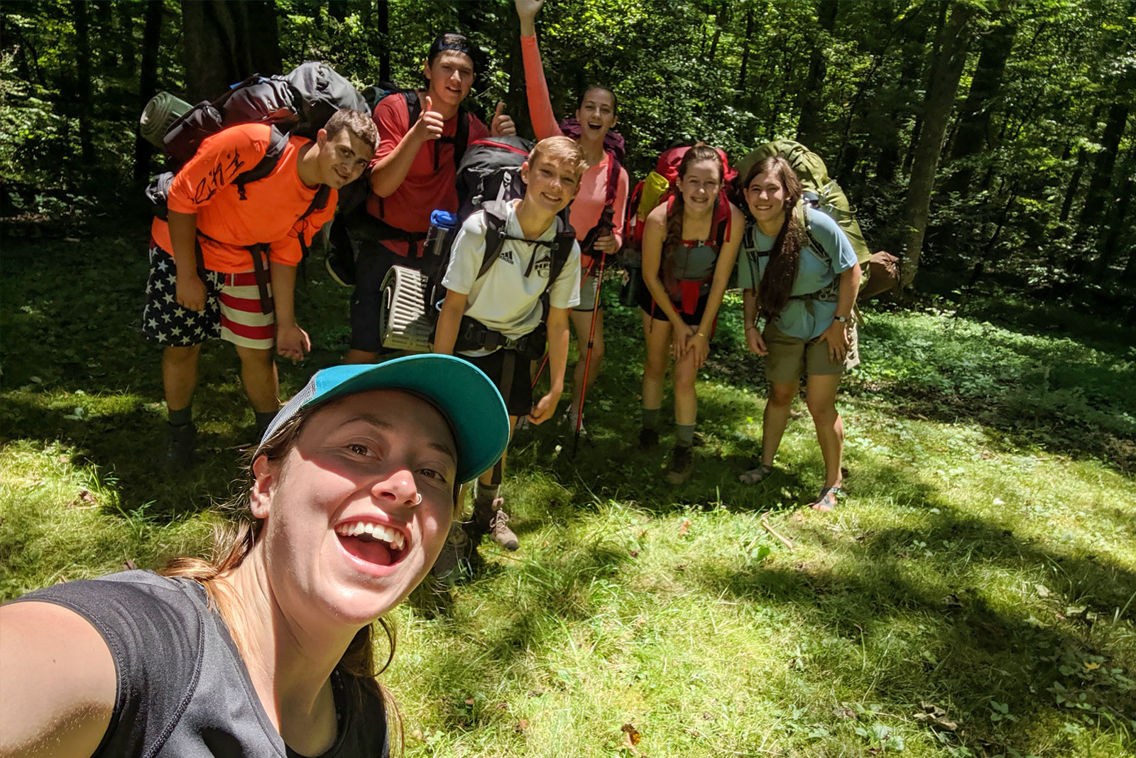 A group of campers wearing backpacks take a selfie