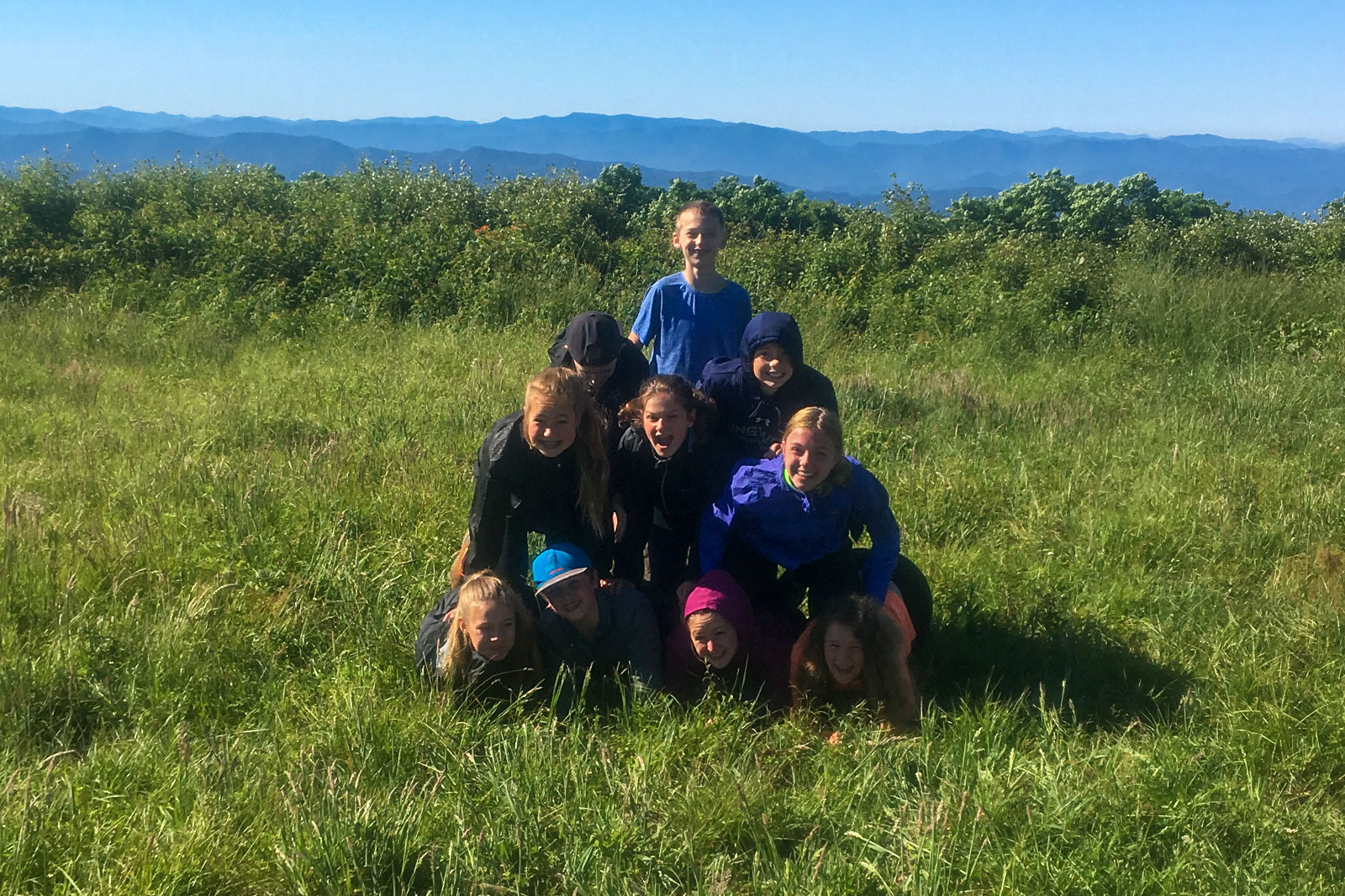 Campers build a human pyramid on top of a mountain