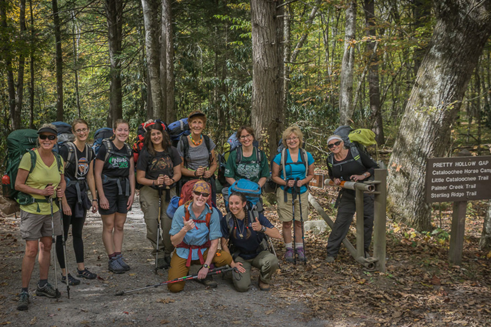 A group of female backpackers pause for a photo at a trailhead