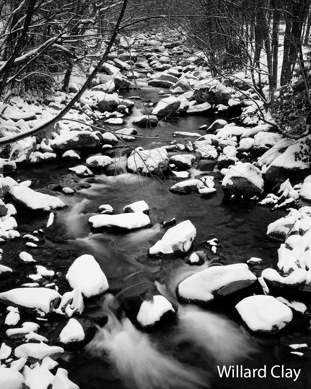 A black-and-white photo of a stream with snow-covered rocks by Willard Clay