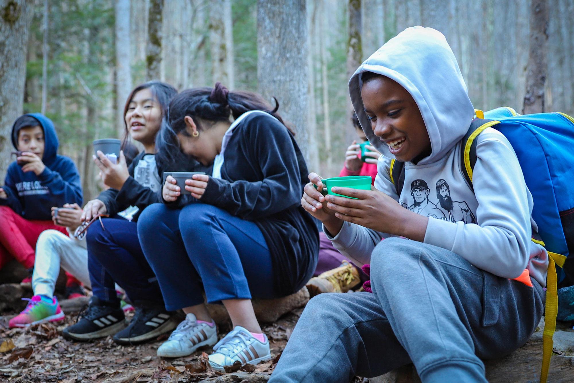 School children laugh around a campfire