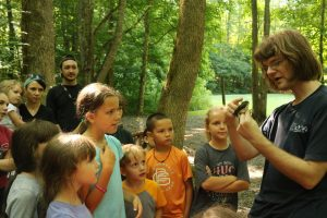 A Tremont Teacher Naturalist holds a bird to show visitors during a bird banding day