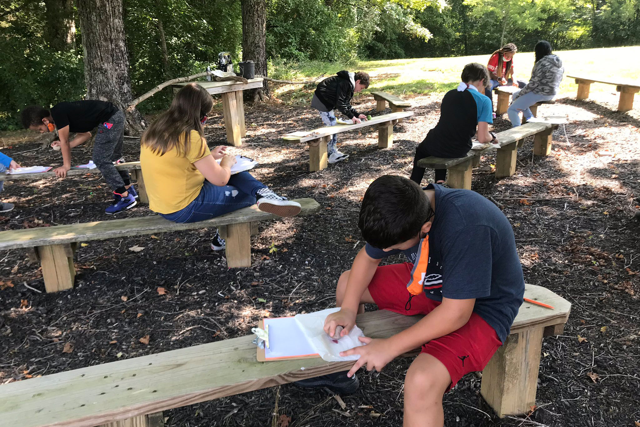 Students journal outside in their schoolyard