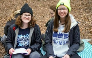 Two students pause from writing observations in nature journals to smile at the camera