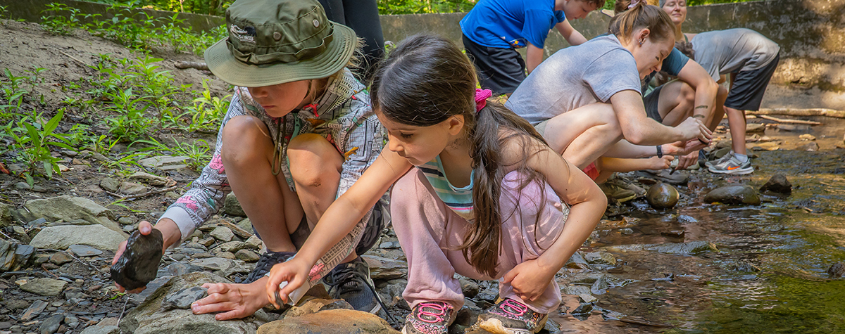 Two kids examine something by the edge of the river, while other families also explore behind them at Tremont's family camp.