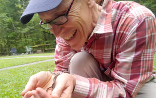Man excitedly holds many tiny baby garter snakes in his hands.
