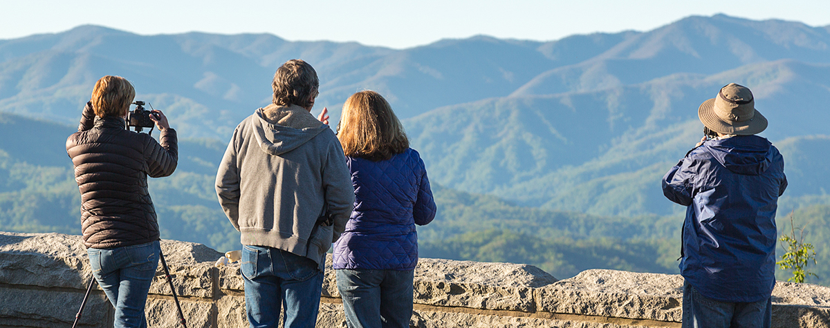 Four people taking photos of the Smoky Mountains in a photography workshop.