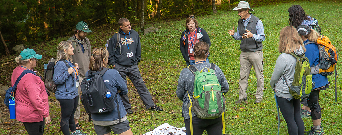 A group of teachers stands in a circle discussing an activity during Teacher Escape Weekend.