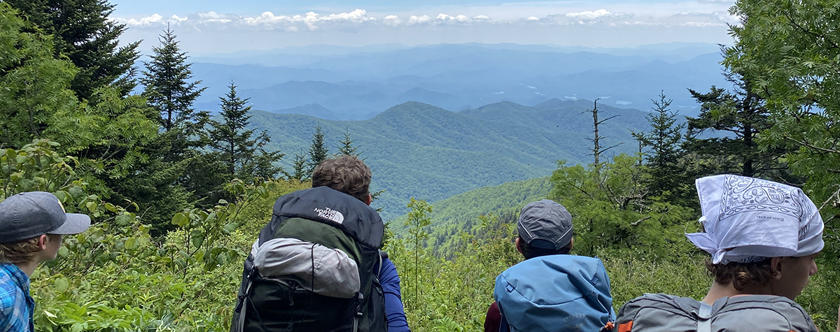 Several teens wearing hiking packs looking at a gorgeous mountain landscape during the Wilderness Adventure Trek