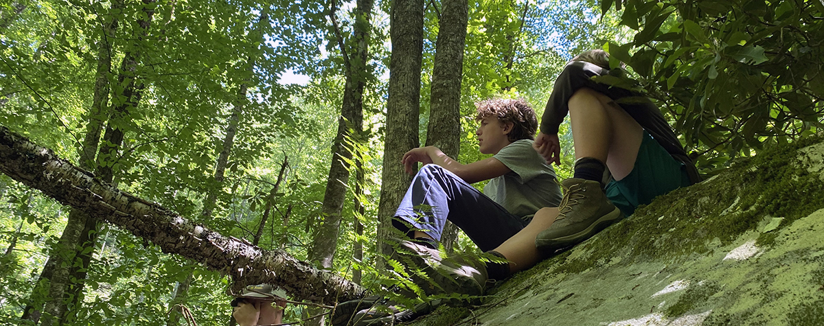 A couple of teens sit on a rock in the woods during the Wilderness Adventure Trek program at Tremont.
