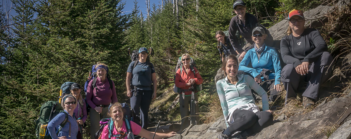 A group of women with backpacks smile while sitting on a rock in Great Smoky Mountains National Park.